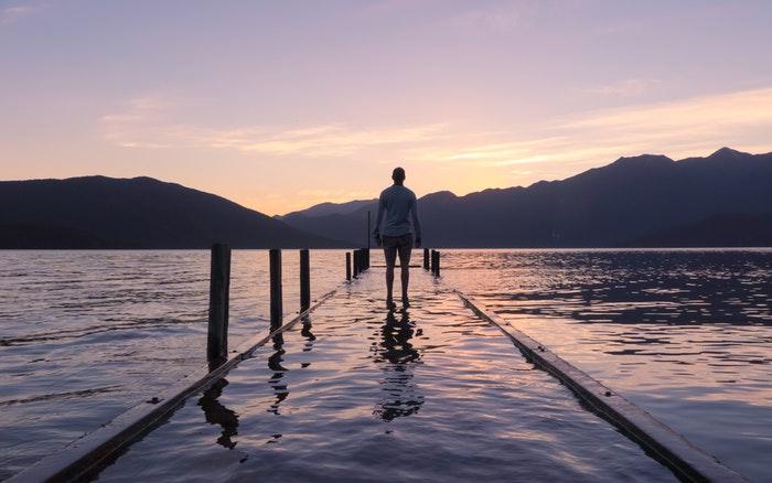 uma imagem de um homem caminhando em direção a um lago ao pôr do sol