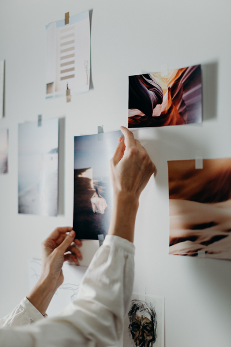 Uma pessoa colando uma imagem impressa na parede.
