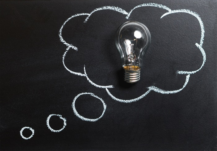 A lightbulb on top of a blackboard drawing of a thought bubble