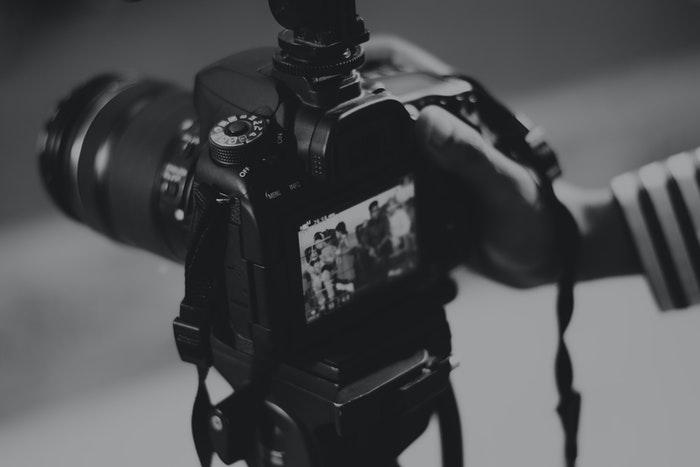 Uma pessoa tirando uma foto com uma DSLR grande