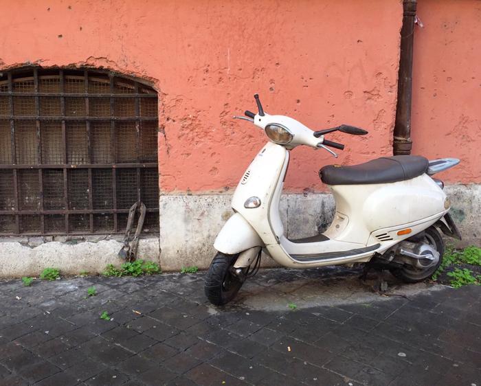 a Vespa motorbike on a street corner in Rome
