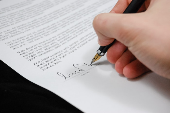 A close up of a person signing real estate photography terms and conditions