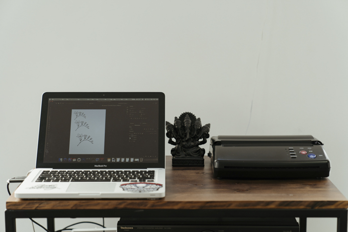 A laptop and printer on a wooden desk