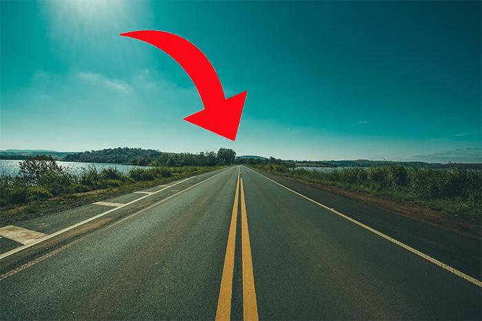 foto de uma estrada vazia com uma seta vermelha mostrando o ponto de fuga na linha do horizonte