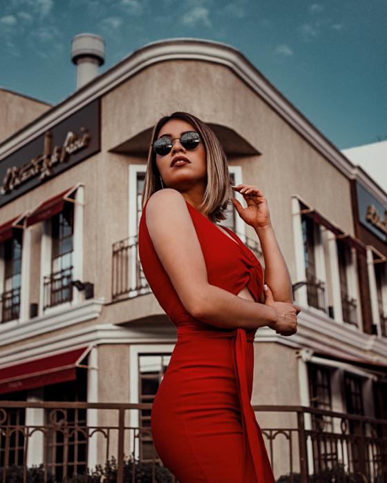 retrato de mulher de vestido vermelho posando em frente a um edifício