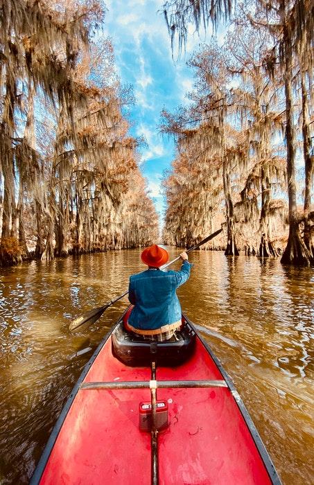 Um homem em um barco a remo descendo um rio.