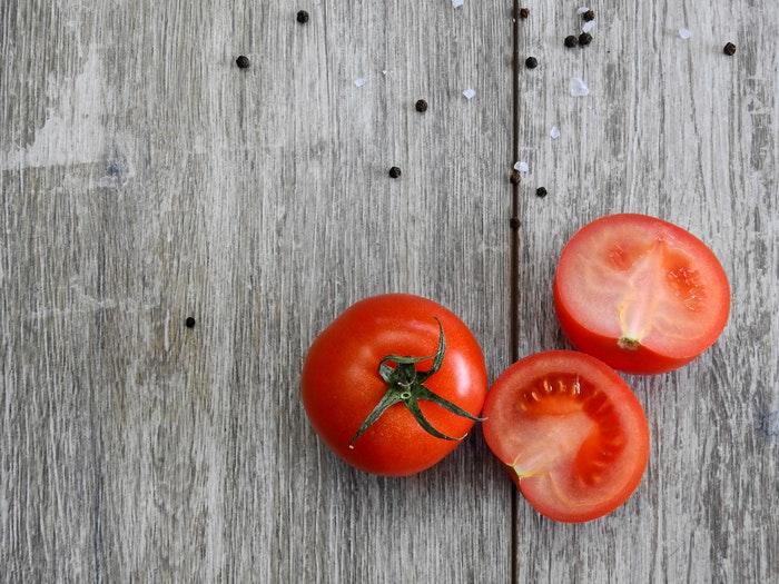 O contraste de cores entre o tomate e a madeira ajuda a criar uma composição equilibrada que chama a atenção.