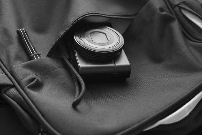Compact camera inside a backpack. Black and White. Close up.