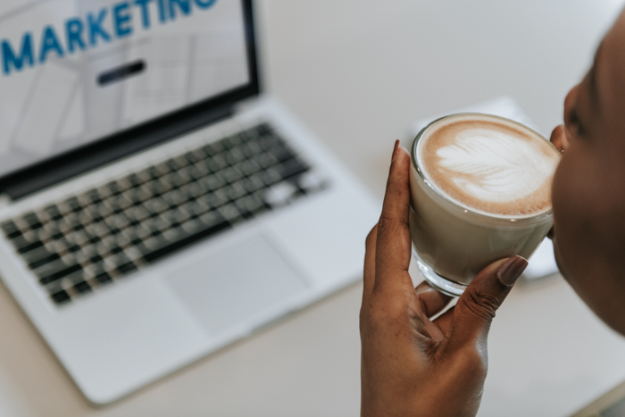 Woman sipping a cup of coffee while working on a laptop