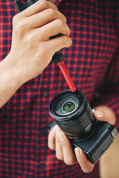 Seorang pria membersihkan lensa kameranya dengan blower hitam dan merah dan larutan pembersih lensa.
