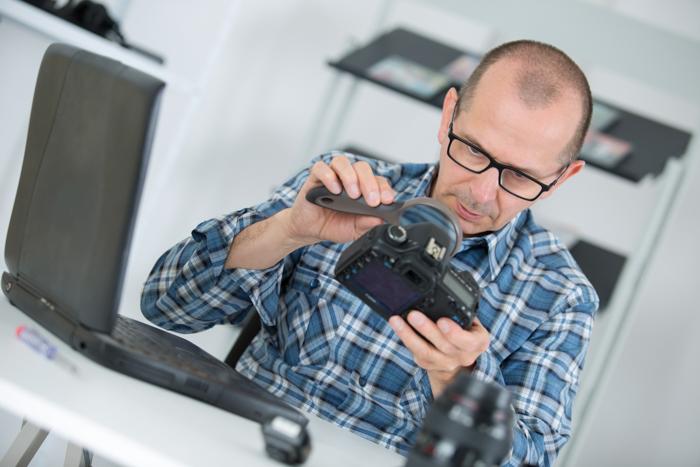 Repairman looking at fungus on a camera lens through magnifying glass