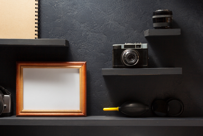 An old camera, a lens, and a picture frame on a wooden shelf