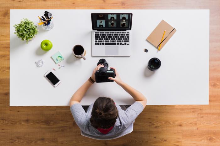 Uma mulher de cima, com uma câmera na mão e com um laptop, um telefone celular, uma maçã e um café na mesa do escritório