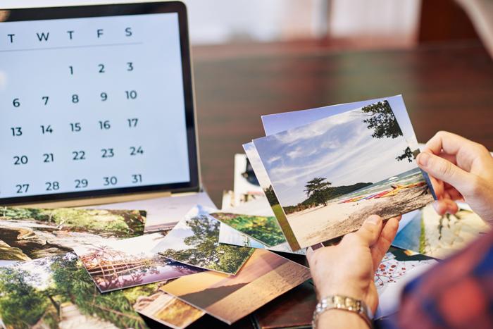 Mãos do viajante revisando fotos que ele imprimiu após as férias de verão