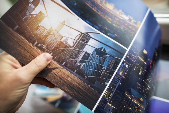 Um homem verificando a qualidade de impressão do álbum de fotos personalizado impresso digitalmente.