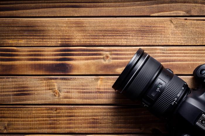 Câmera profissional com lente na mesa de madeira.