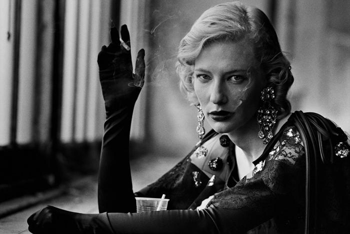 Retrato em preto e branco de uma mulher elegante, fumando e olhando para a câmera