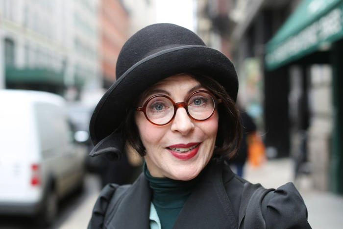 A portrait of a woman with black hat and red glasses
