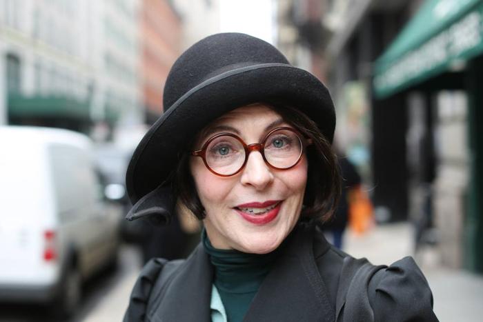 Retrato de uma mulher com chapéu preto e óculos vermelhos