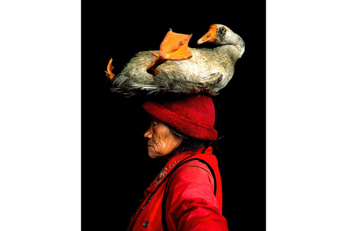 An old lady in red clothes and a hat, and a goose on top of the hat.
