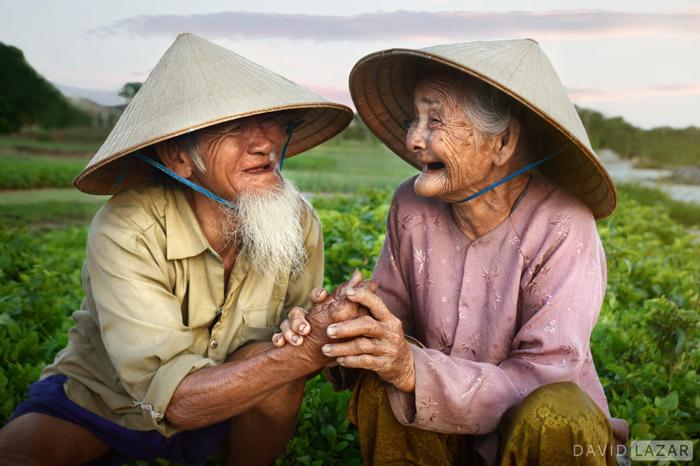 Um casal de idosos asiáticos rindo um do outro