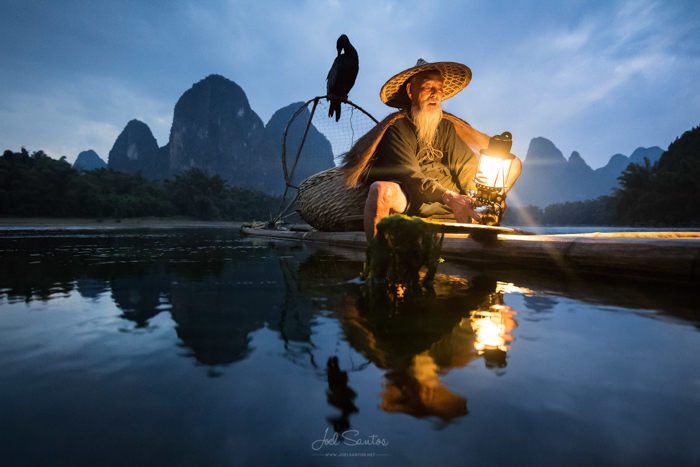 Um pescador asiático e um corvo-marinho