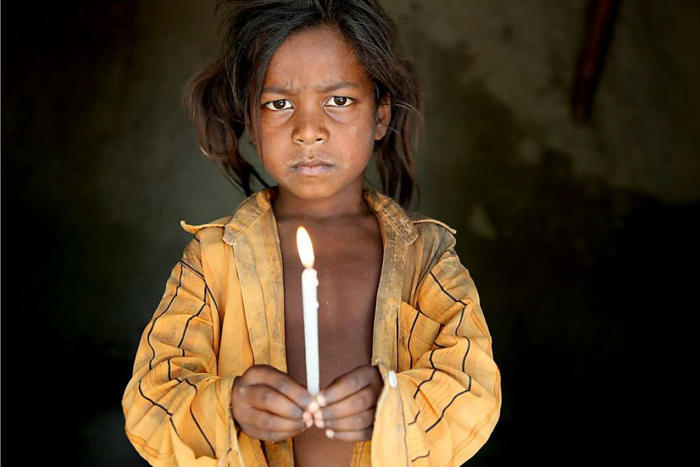 A little child holding a candle, wearing a yellow shirt.