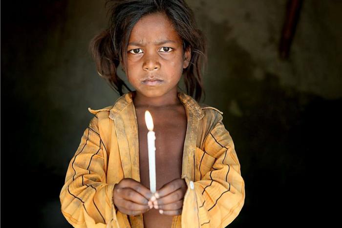 Um menino segurando uma vela, vestido com uma camiseta amarela.