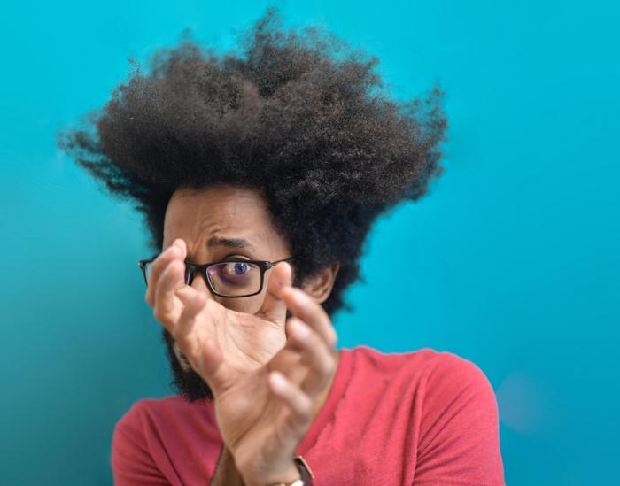 πορτρέτο ενός νεαρού μαύρου με γυαλιά κοιτάζοντας μέσα από τα χέρια του