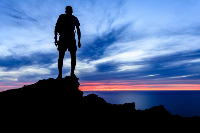 Ο άνθρωπος πεζοπορία σιλουέτα σε βουνά, ηλιοβασίλεμα και ωκεανό πάνω από τον όμορφο μπλε ουρανό. Αρσενικός πεζοπόρος που περπατά στην κορυφή του βουνού που βλέπει το τοπίο νύχτας ομορφιάς.