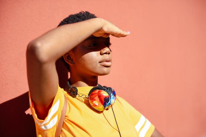Νέα μαύρη γυναίκα που καλύπτει με το χέρι τον ήλιο που πέφτει στα μάτια της. Κορίτσι με πολύ κοντά μαλλιά.