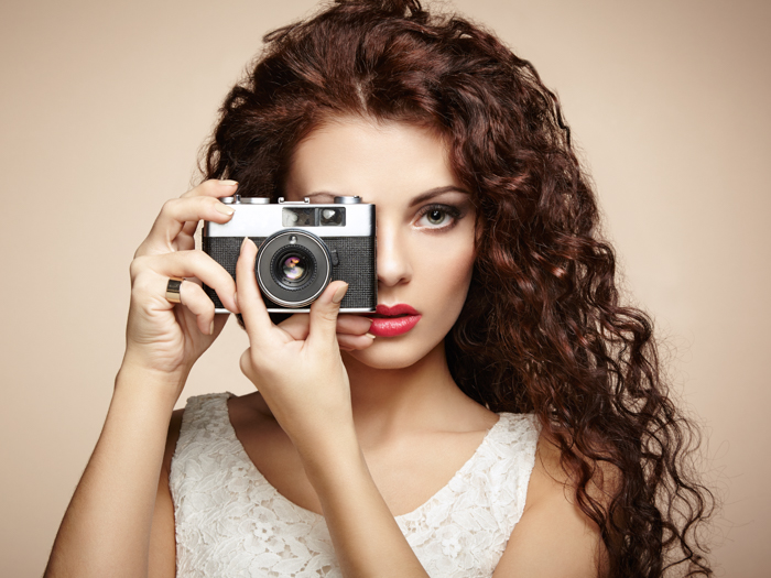 φωτογραφία μιας γυναίκας που κρατά μια κάμερα πάνω από ένα μάτι
