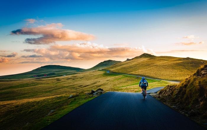 Um ciclista em uma estrada em uma bela área rural