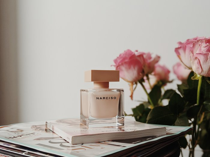 Product photo of perfume on a desk beside pink roses
