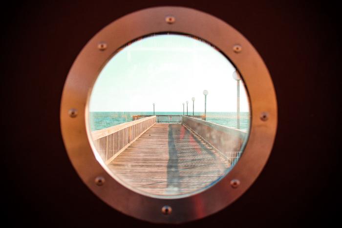 Vista de um píer através da vigia de um navio