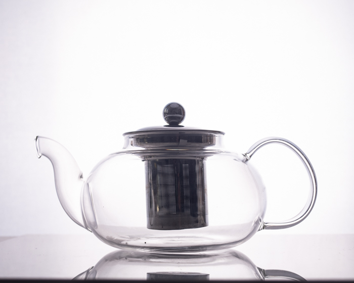 glass teapot with dark metal reflective surface interior