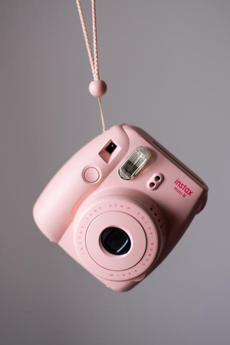 Uma imagem de uma câmera instantânea de filme instantâneo fujifilm instax mini 8 rosa pendurada em sua alça