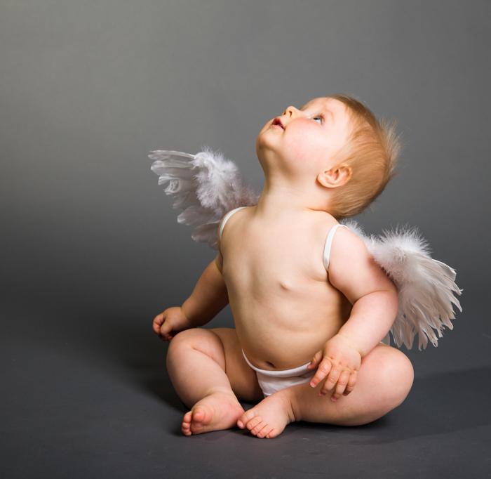 Doce foto de Natal de um bebê vestido com asas de anjo