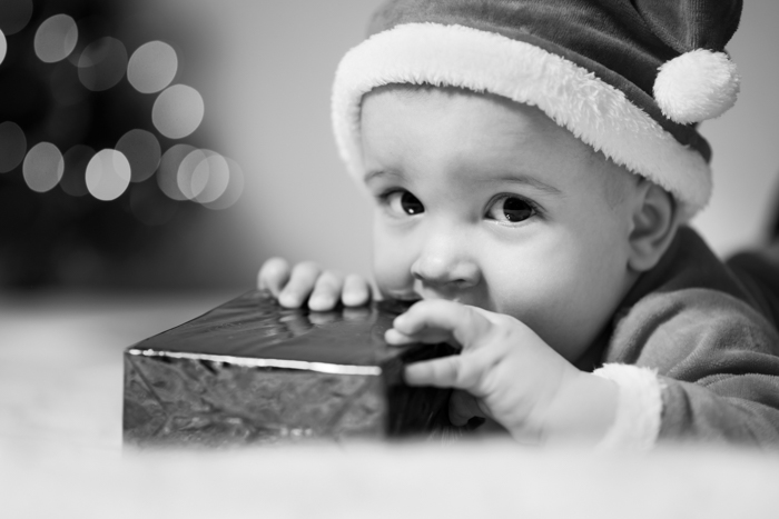 Black and white Christmas portrait of a young boy with a present