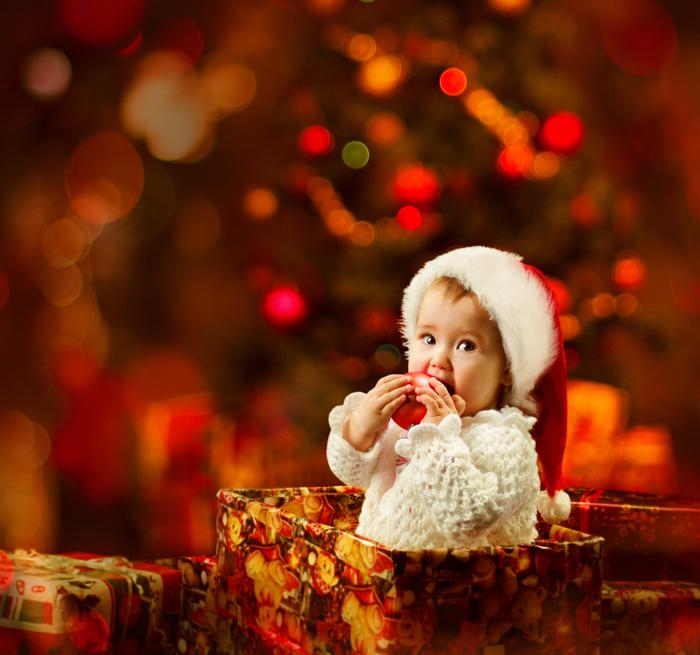Doce foto de Natal de um bebê em uma caixa de presente na frente da árvore de Natal