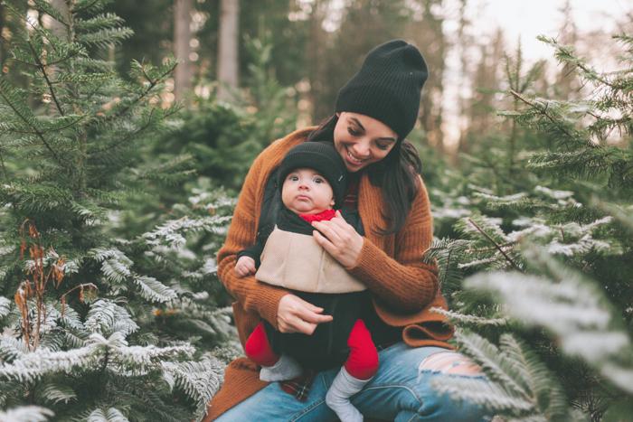 Doce foto de Natal de uma mulher segurando seu bebê em frente a uma árvore de Natal ao ar livre