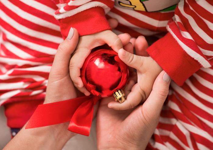 Foto de um casal segurando as mãos de seus bebês com uma decoração de Natal