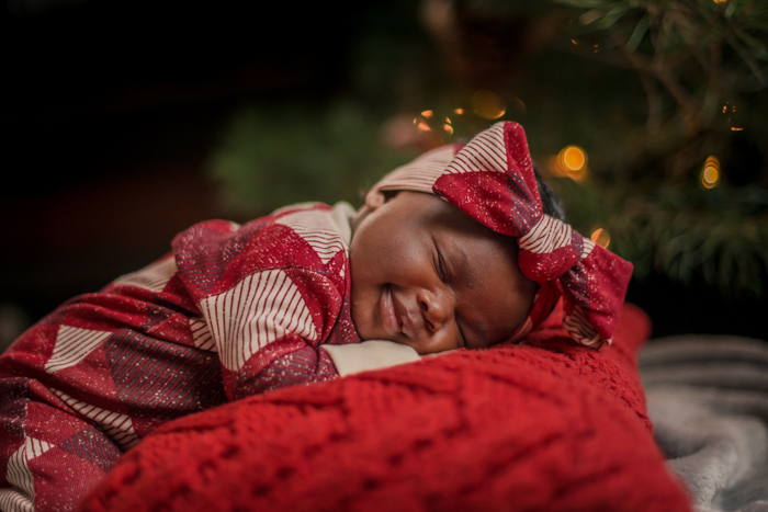 Sweet baby's first Christmas portrait by the christmas tree