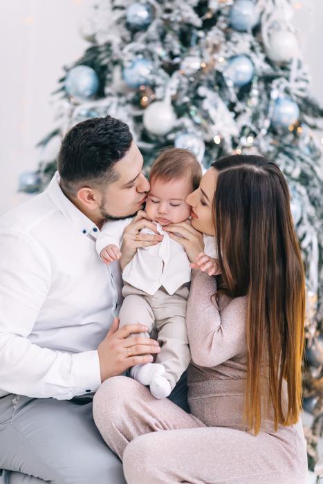 Doce primeira foto de Natal de um casal segurando seu bebê na frente da árvore de Natal