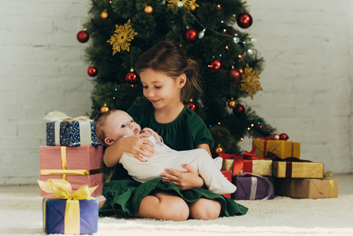 A little girl holding a newborn baby for their first christmas photo shoot