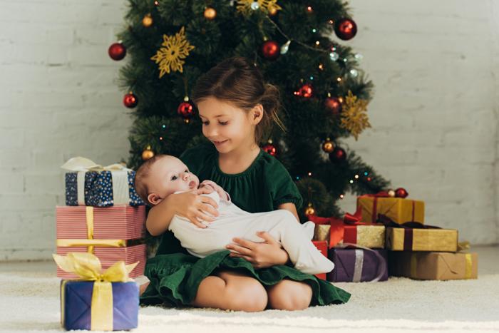 Uma menina segurando um bebê recém-nascido para sua primeira sessão de fotos de Natal
