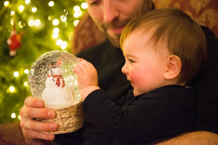 Doce foto de Natal de um pai e um bebê em frente à árvore de Natal