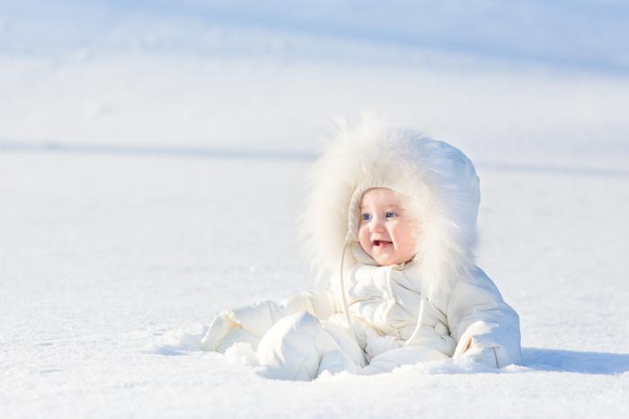 Doce foto de Natal de um bebê na neve.