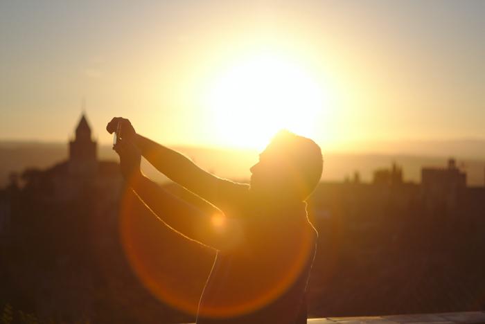 uma imagem de um homem em um telhado com luz de fundo e reflexo de lente