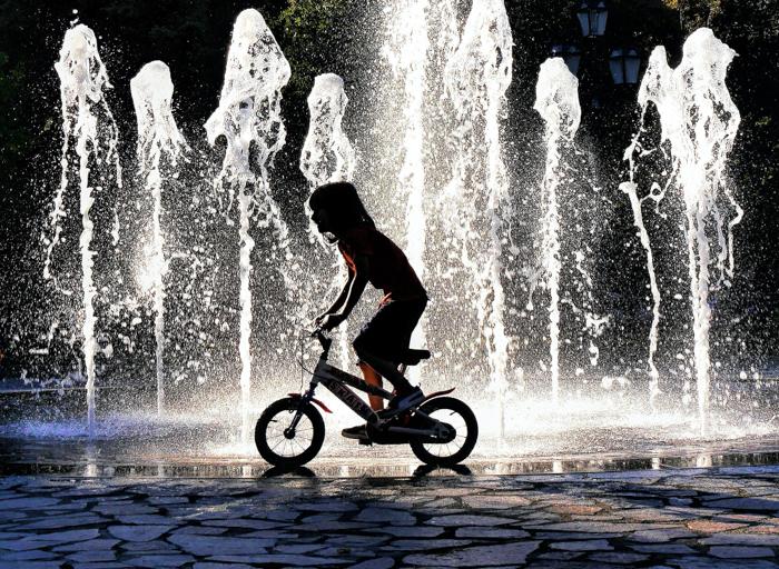 uma imagem de um menino andando de bicicleta em frente a uma fonte iluminada por trás